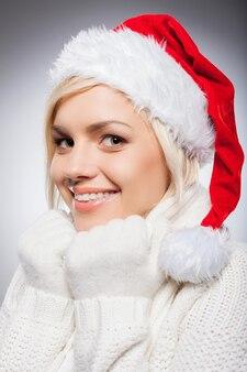 Ragazza con cappello da babbo natale. bella giovane donna con cappello da babbo natale che guarda l'obbiettivo e sorride mentre è isolata su gray