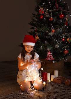Una ragazza con un cappello da babbo natale si siede sotto un albero di natale e tiene tra le mani delle luminose luci di natale accese.
