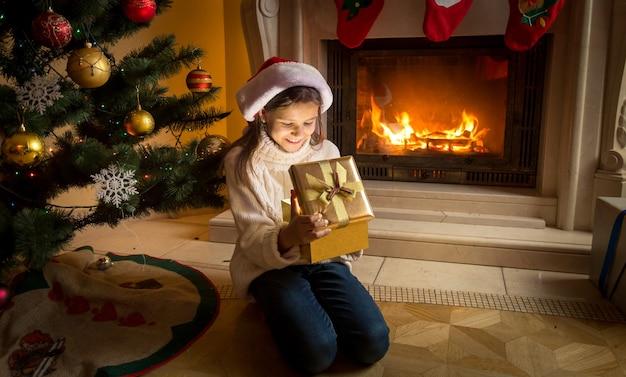 Ragazza con cappello da babbo natale seduta davanti al caminetto acceso e guardando dentro la scatola regalo di natale