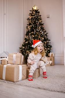 Ragazza in cappello della santa con il regalo di natale sulla priorità bassa dell'albero di natale. bambino con regalo di natale a casa.
