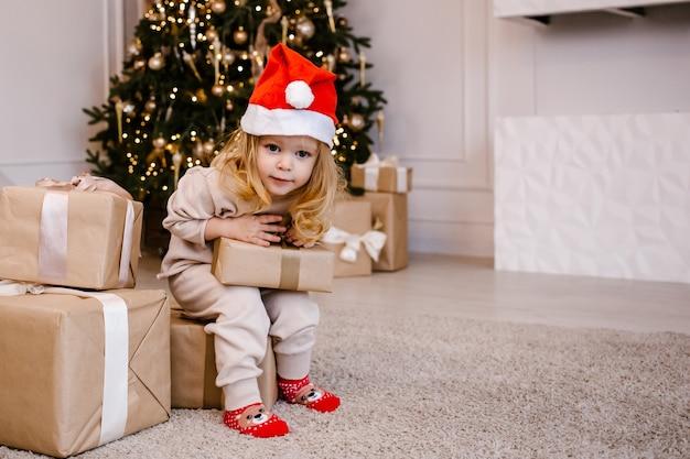 Ragazza in cappello della santa con il regalo di natale sulla priorità bassa dell'albero di natale.