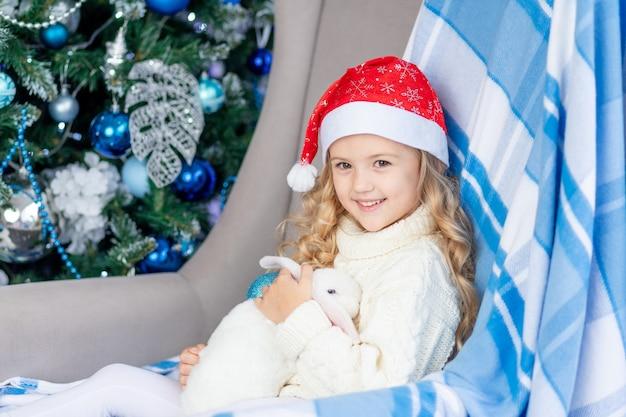 Una ragazza con un cappello da babbo natale con un coniglio bianco a casa vicino all'albero di natale, il concetto di nuovo anno e natale