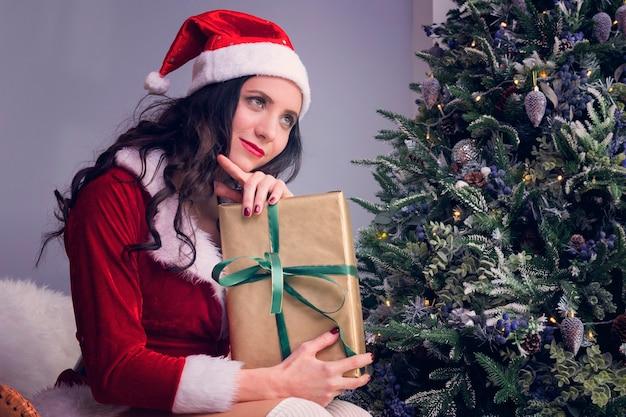 Una ragazza travestita da babbo natale sogna un regalo per natale. giovane donna che tiene un regalo sullo sfondo di un albero di natale e guarda pensierosa fuori dalla finestra in attesa di un miracolo.