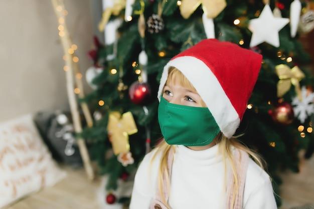 Ragazza con cappello e maschera di babbo natale, periodo natalizio, isolamento durante le vacanze, covid-19, coronavirus.