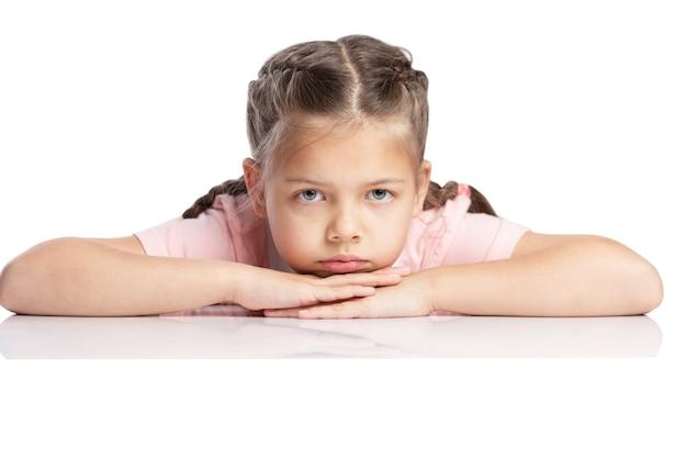 Una ragazza in età scolare con le trecce si trova al tavolo. fatica e stress isolato su sfondo bianco.