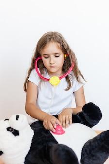 Ragazza, ragazza della scuola tratta il suo orso giocattolo, panda, orso si è ammalato, gioca al dottore, veterinario, ruolo, cresce, impara nel gioco