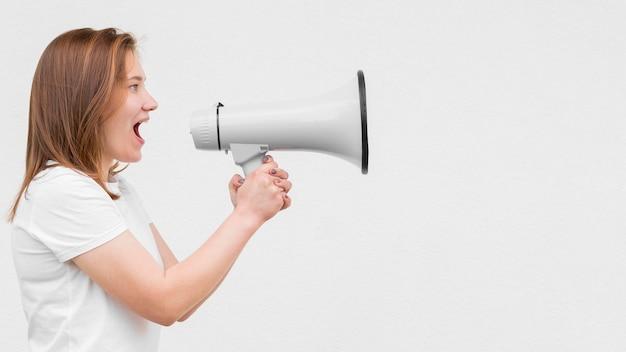 Ragazza che grida nello spazio della copia del megafono