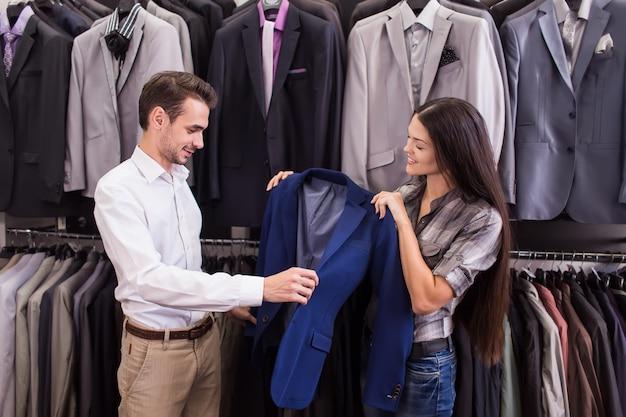 Il venditore di ragazze aiuta a prendere un cliente in una boutique di abbigliamento da uomo