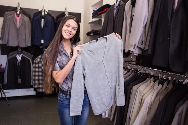Il venditore di ragazze offre al cliente di provare un cardigan nella boutique di abbigliamento maschile
