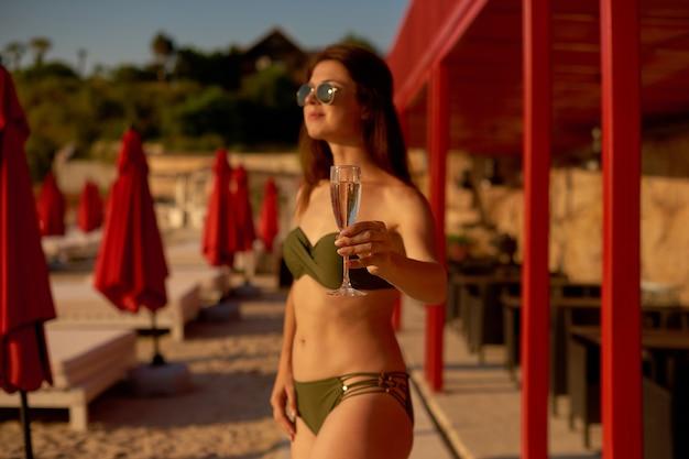 La ragazza in costume da bagno separato con il bicchiere in mano sulla spiaggia della città sta riposando