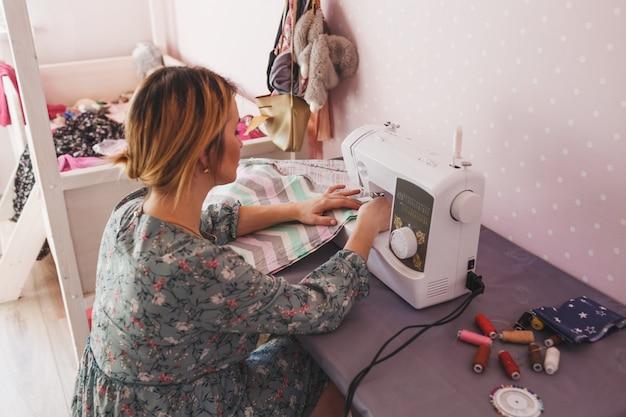 Una ragazza cuce su una macchina da cucire a casa. la vista posteriore è un hobby preferito. produzione propria di abbigliamento.