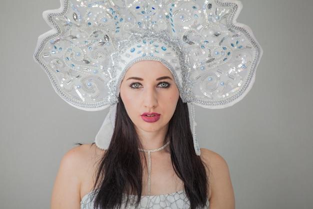 Una ragazza in un costume sexy di capodanno della fanciulla di neve nel kokoshnik russo