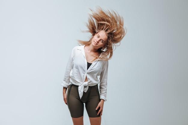 La ragazza scuote i capelli su uno sfondo grigio