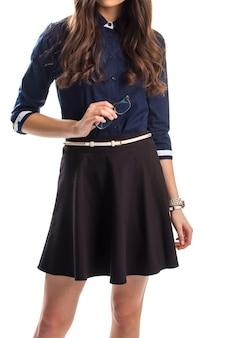 La ragazza in camicia tiene gli occhiali. gonna nera con cintura bianca. intelligenza e bellezza. segretaria ben vestita.