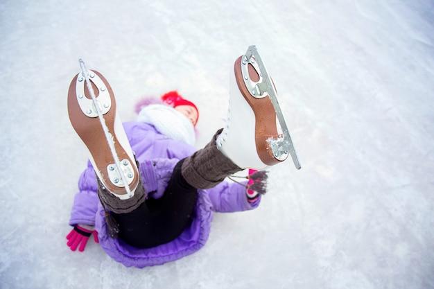 Una ragazza, calzata con i pattini, giace sul ghiaccio con le gambe sollevate, concentrandosi sui pattini.