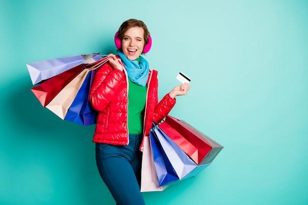 Ragazza centro commerciale client hipster funky studente tenere borse pagare carta di debito ammiccare lampeggiare consigliare affare tuta sportiva maglione verde rosa pantaloni blu pantaloni isolato verde acqua muro