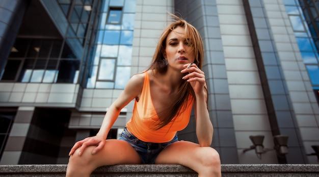 Ragazza in pantaloncini fumare per strada. panorami di banner