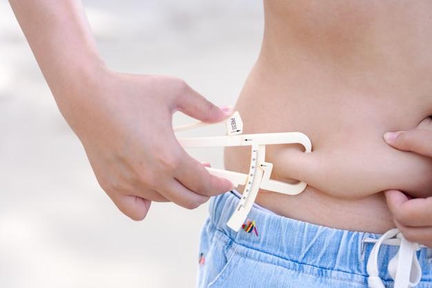 La ragazza mostra tenendo e spingendo la pelle della cellulite della pancia con il tester grasso corporeo personale