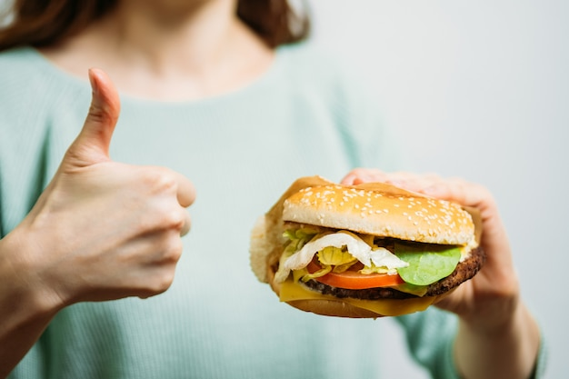 La ragazza mostra come un hamburger. il concetto di un ottimo hamburger.