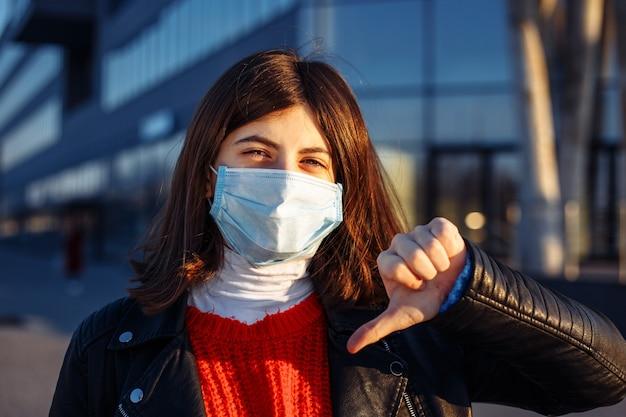 La ragazza mostra il pollice verso il basso e non ama la pandemia mondiale del coronavirus