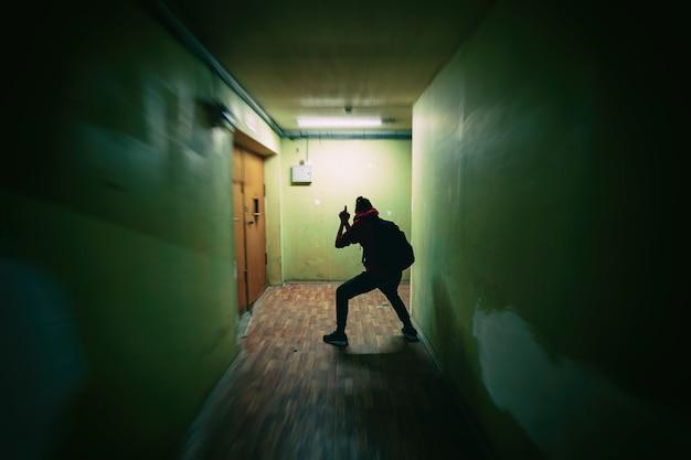 La siluetta della ragazza imita la riproduzione di una spia con una pistola. corridoio scuro. in agguato, furtivamente, spaventoso