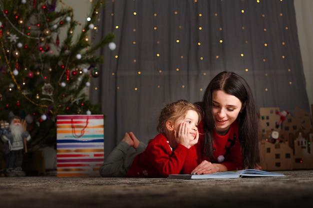 Una ragazza e una sorella stanno leggendo un libro vicino all'albero di natale a casa. la famiglia legge fiabe per il nuovo anno.
