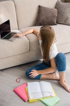 La ragazza si siede sul pavimento con libri e laptop sul divano