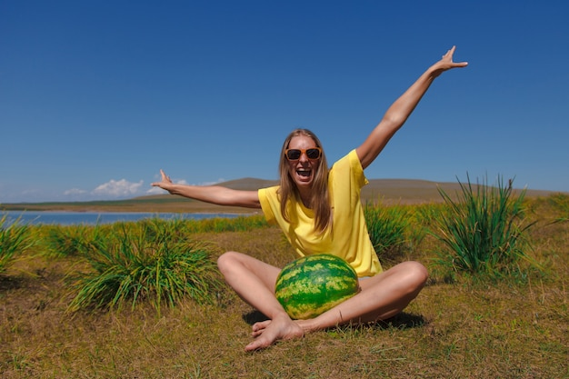 Una ragazza si siede sulla spiaggia e tiene in mano un'anguria. maturazione delle bacche estive emozioni e umore gioiosi. picnic estivo.