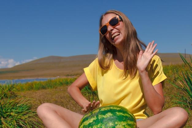 Una ragazza si siede sulla spiaggia e tiene in mano un'anguria che matura bacche estive emozioni e umore gioiosi ...