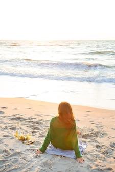 Una ragazza si siede sulla spiaggia e versa del vino in un bicchiere, ammira l'alba. bella mattina.