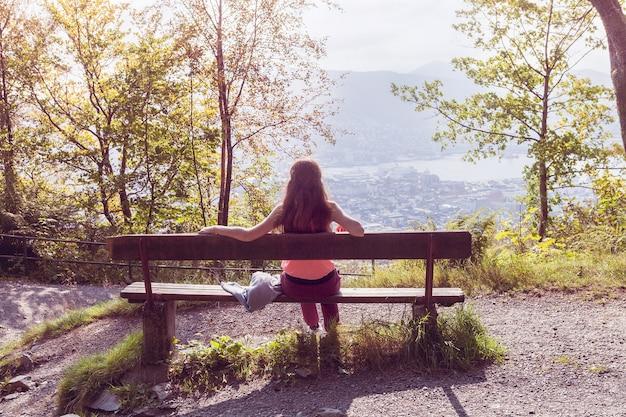 La ragazza si siede su una panchina nel bosco, di spalle alla telecamera e davanti a lei si apre un panorama della città