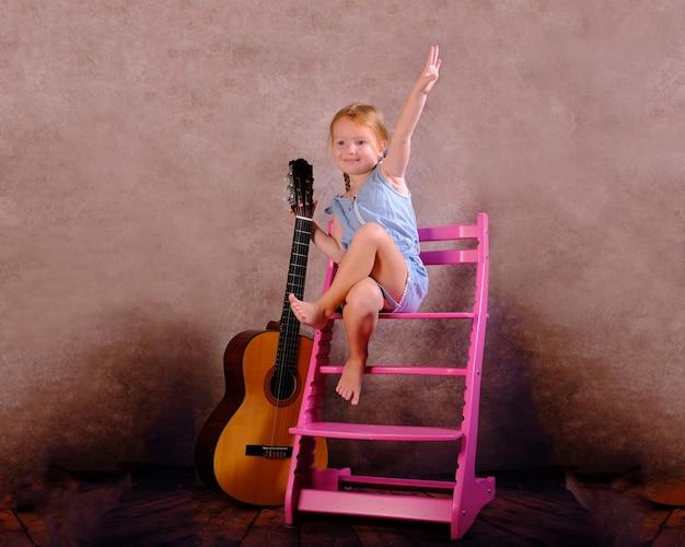 La ragazza si siede su una sedia e tiene in mano una chitarra