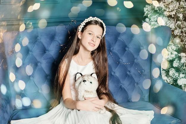 Una ragazza si siede sul divano a natale, hugs cane giocattolo