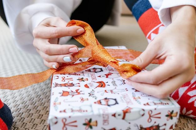 La ragazza si siede sul pavimento e lega un nastro mentre avvolge un regalo. mani che legano il nastro sulla confezione regalo. preparazioni natalizie e confezioni regalo. messa a fuoco selettiva.