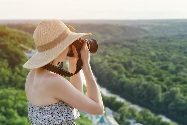 La ragazza si siede sulla collina e scatta foto contro di una foresta e un fiume