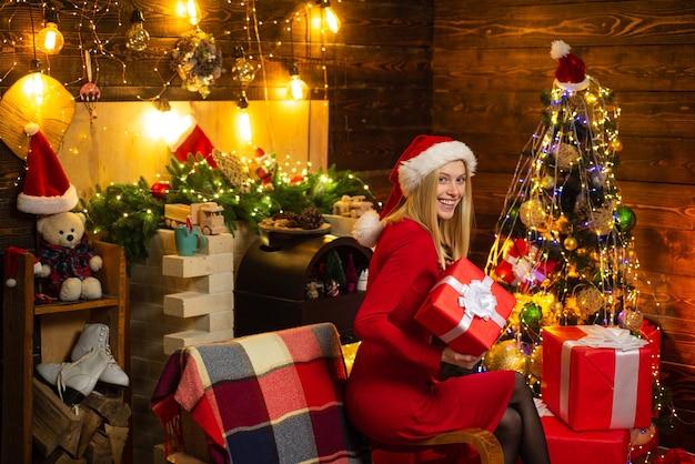 La ragazza si siede vicino all'albero di natale, ai regali e al camino in abiti domestici. atmosfera natalizia. stato d'animo di capodanno. donna attraente in una stanza di natale.