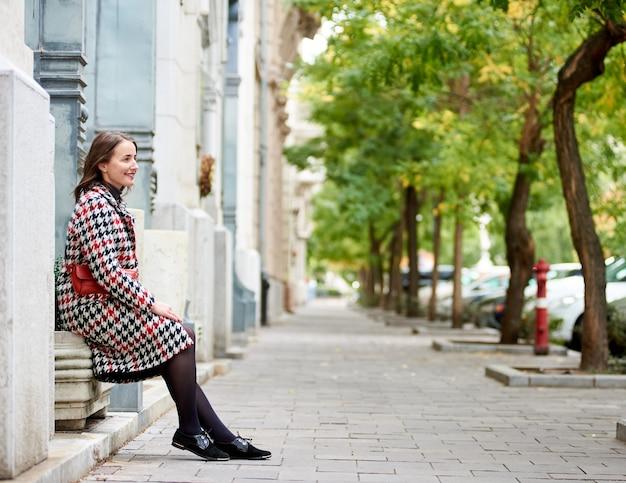 La ragazza si siede vicino al muro di profilo