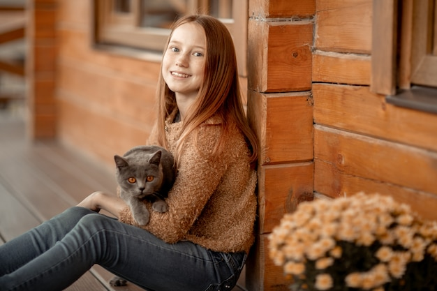 Una ragazza si siede sotto il portico di una casa di legno.