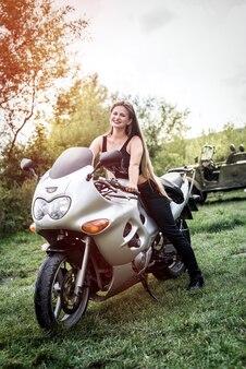 La ragazza si siede sulla bici sportiva sullo sfondo del lago