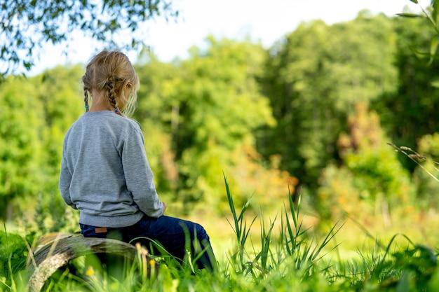 La ragazza si siede con la schiena e guarda in lontananza nella natura.