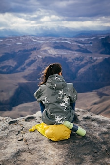 La ragazza si siede su uno zaino giallo sul bordo della scogliera e gode della natura della montagna, nel tè caldo del thermos
