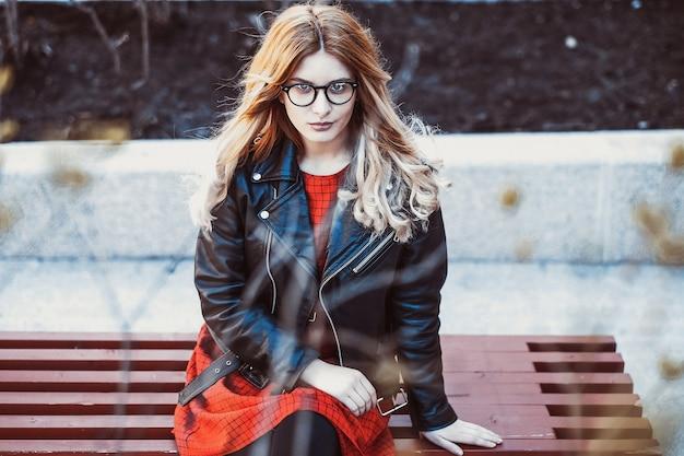 Ragazza seduta sulla panchina. moda di strada. stile di vita urbano. giovane bella donna che cammina all'aperto. immagine tonica.