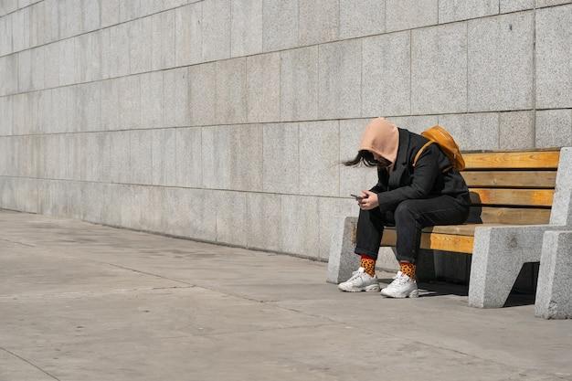 Ragazza seduta su una panchina per strada e scrivendo un messaggio al telefono con la felpa addossoie