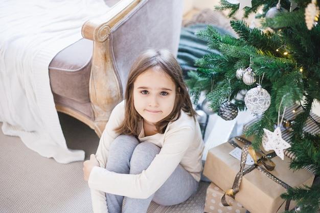 Ragazza seduta accanto all'albero di natale a casa