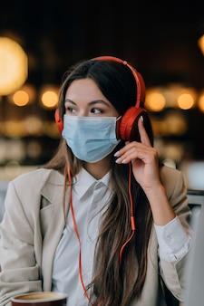 Una ragazza seduta in una caffetteria con le cuffie focolaio di coronavirus