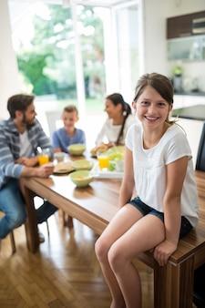 Ragazza seduta sul tavolo da pranzo mentre la famiglia fa colazione