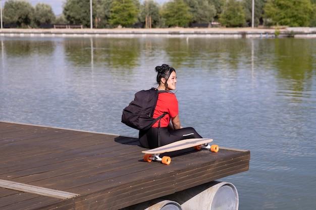 Ragazza seduta su un molo da un lago, con lo zaino
