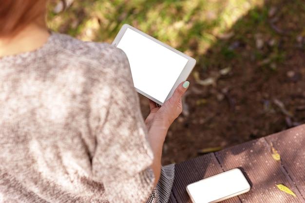 Ragazza che si siede in un maglione lavorato a maglia nel parco che tiene una tavoletta digitale e uno smartphone con un bianco