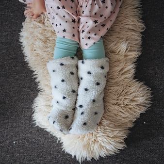 Ragazza che si siede sulla pelle d'agnello sul pavimento