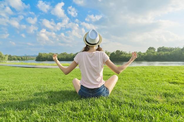Ragazza seduta nella posizione del loto sull'erba verde, vista posteriore, meditazione sul bellissimo paesaggio, spazio cielo blu tra le nuvole, spazio di copia